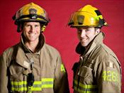 Two Firemen Standing Against a Red Background