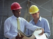 Two Men Wearing Heard Hats Looking At Plans at Construction Site